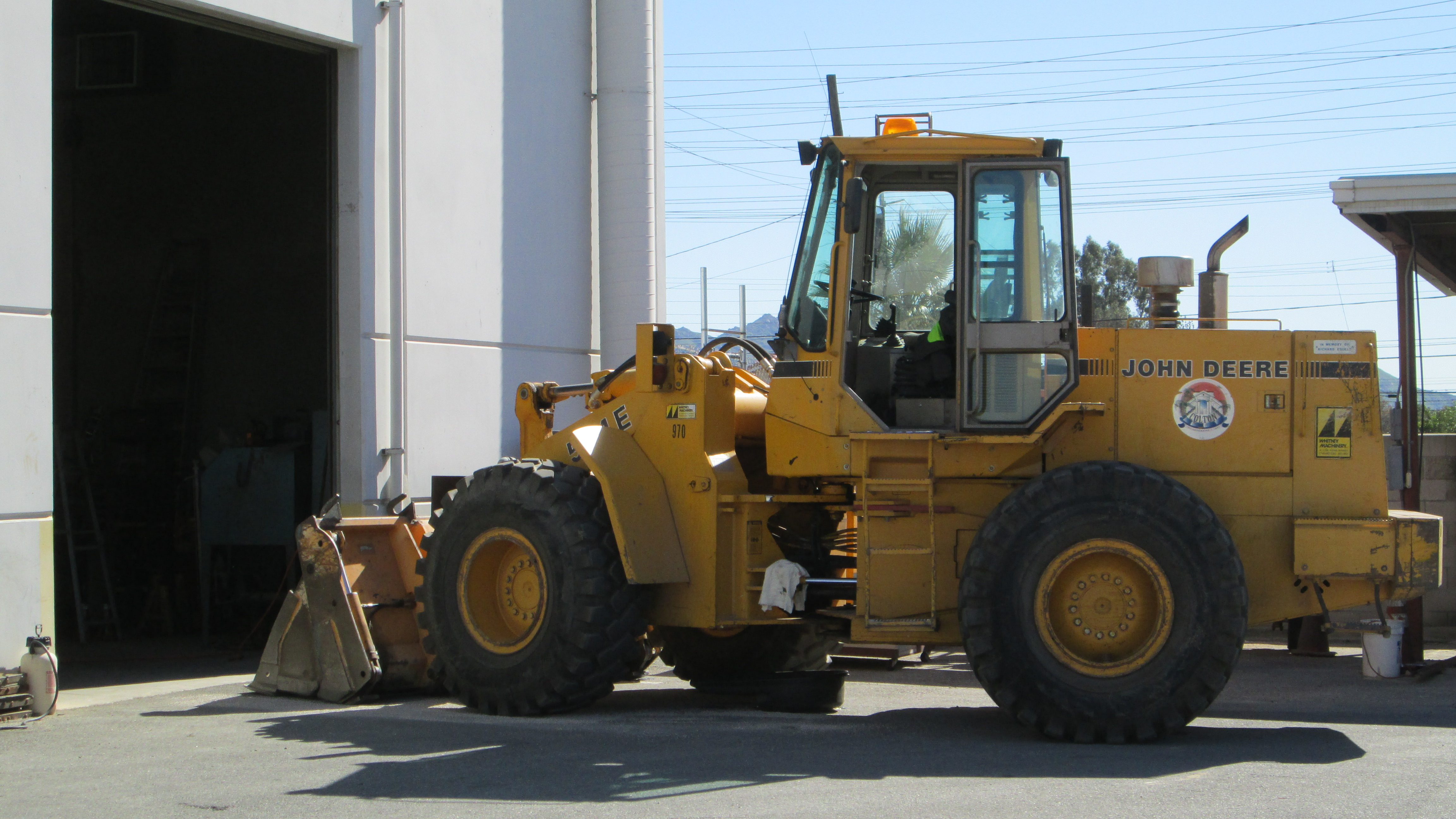 A large piece of construction equipment parked outside of a large garage facility
