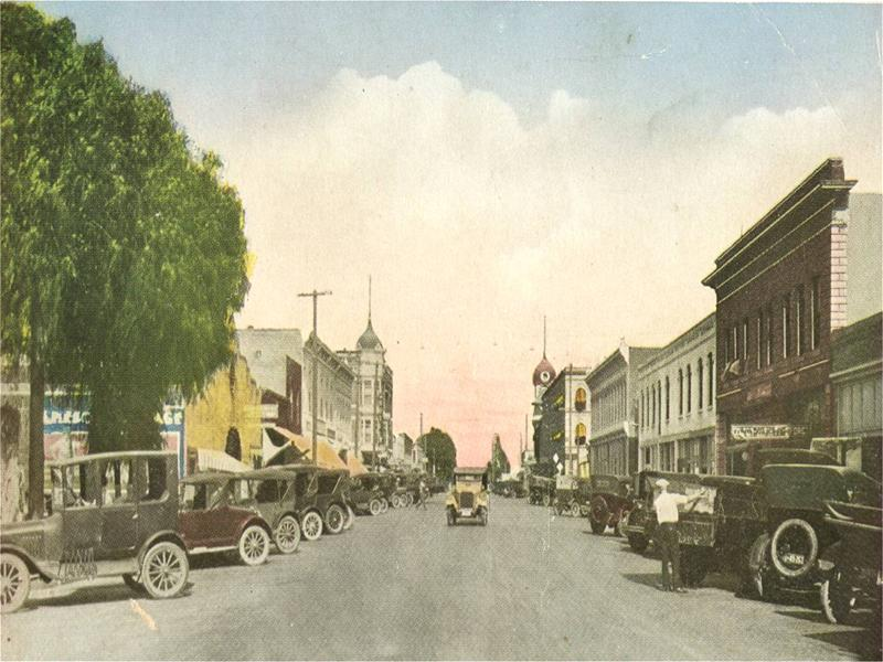 An older image of a city street lined with old-time cars