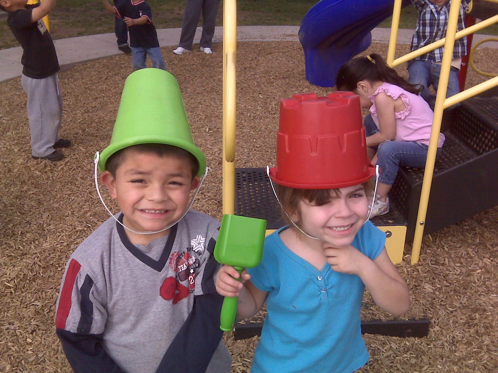 Two young children playing with buckets on their heads
