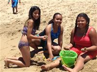 Three teenage girls playing in the sand
