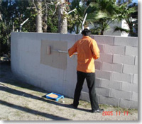A man cleaning a block wall