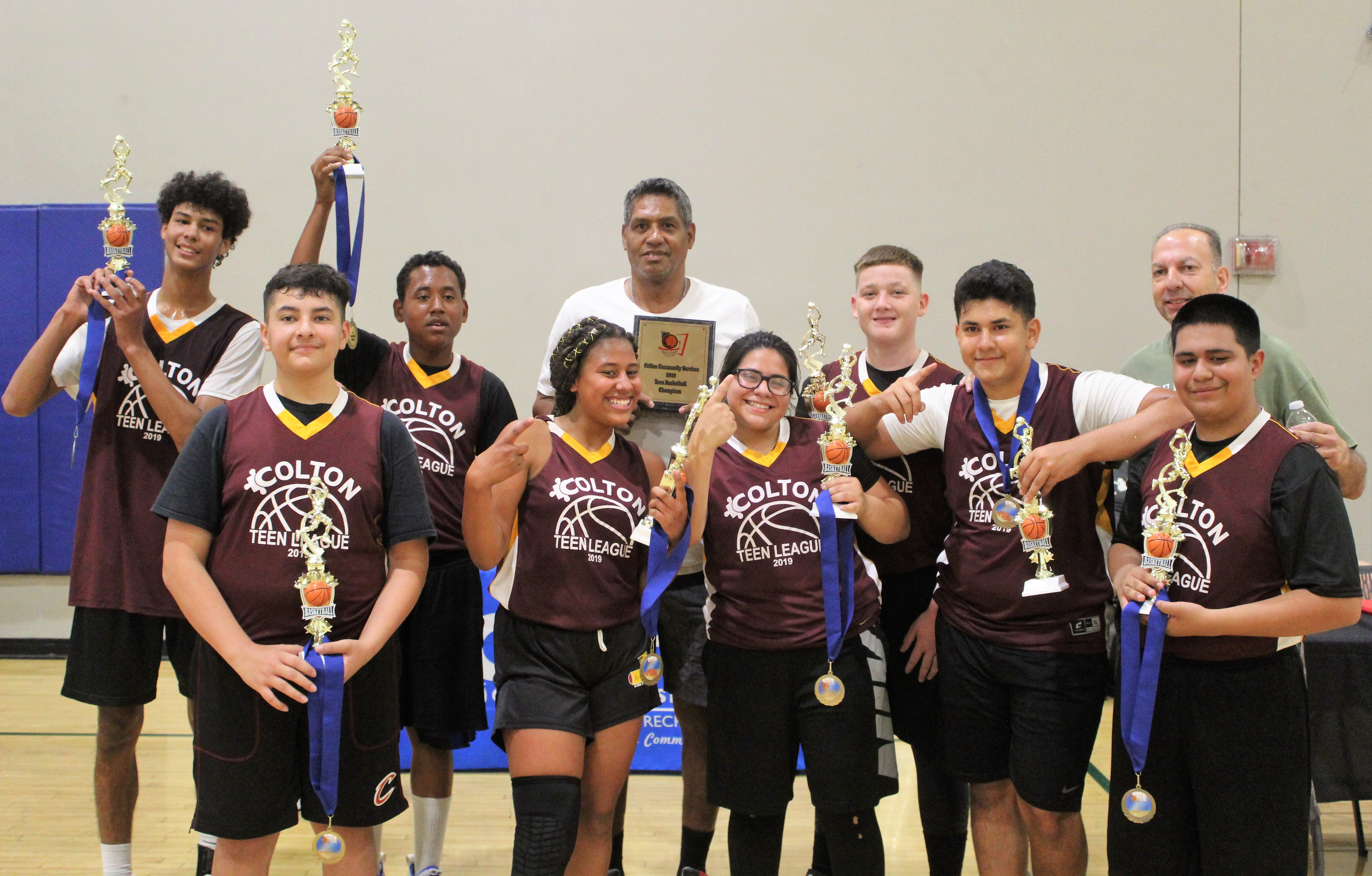 A teen coed basketball team showing off their medals