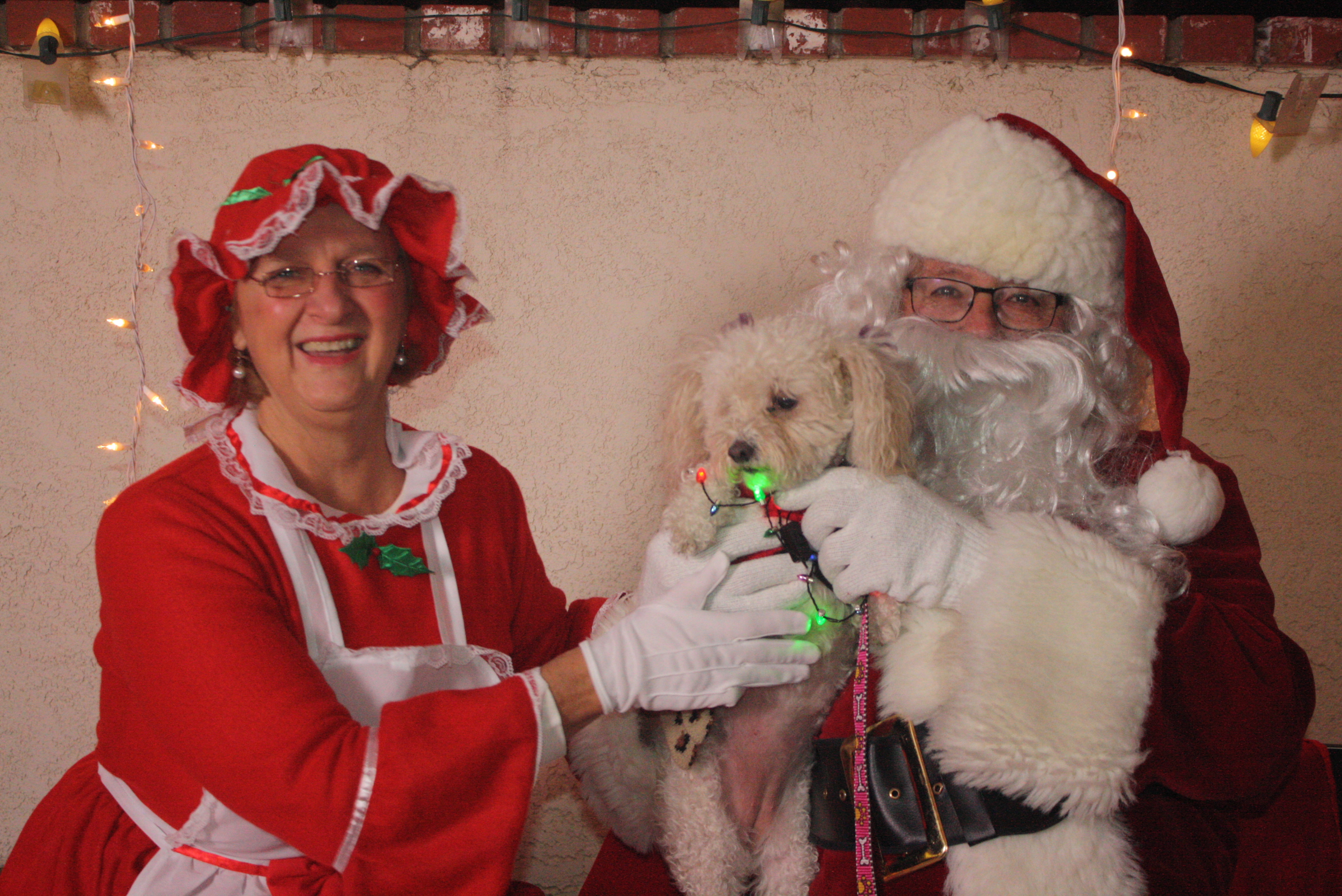 Santa and Mrs. Clause holding a white dog
